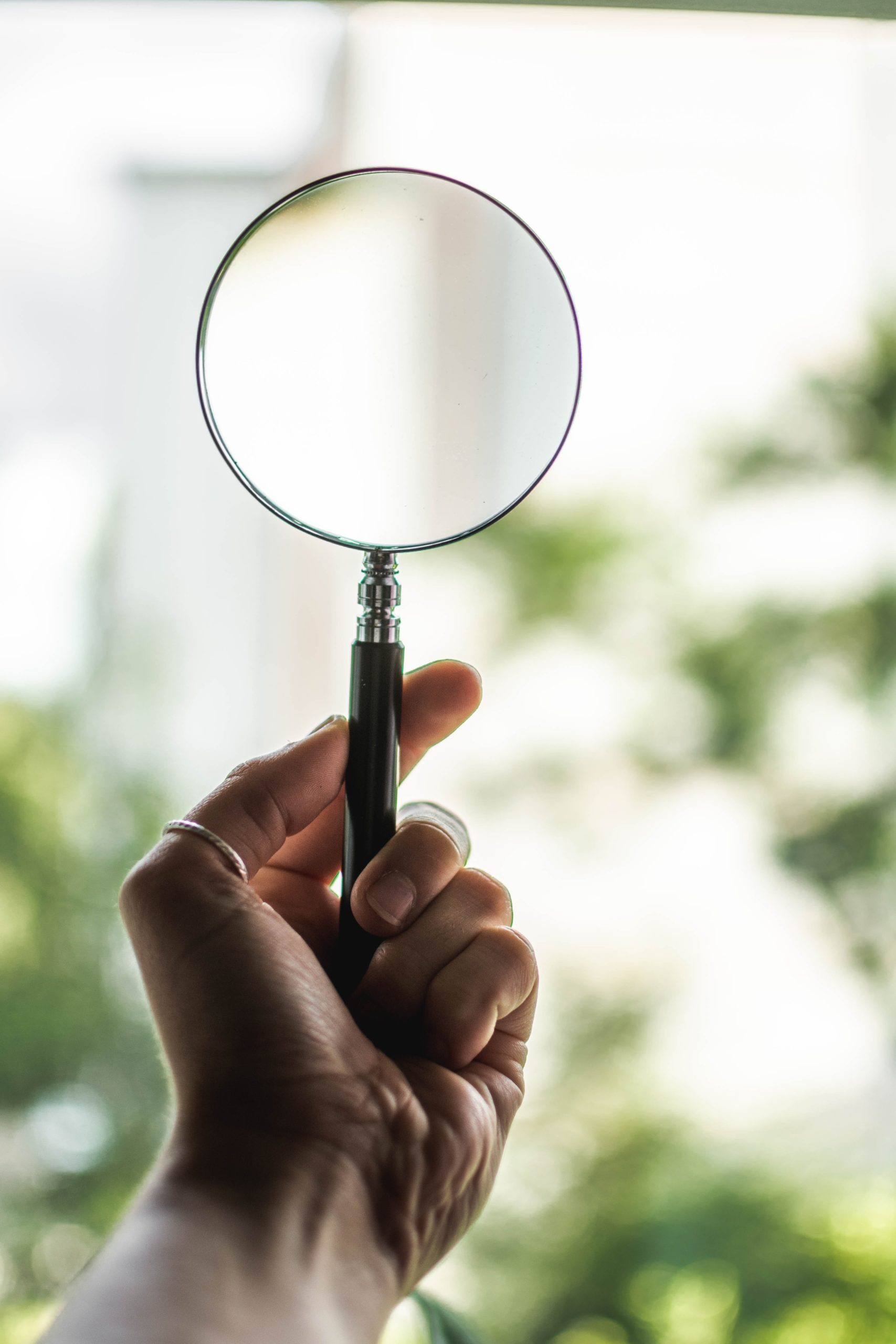 tilt-shift-lens-photography-of-person-holding-magnifying-1192333